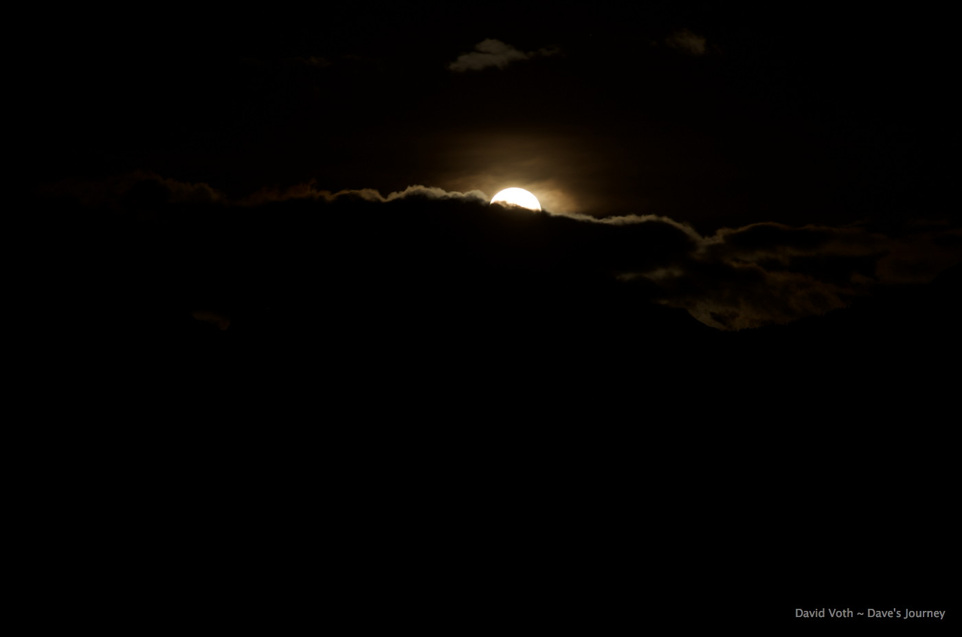 photo of moon rising from behind clouds